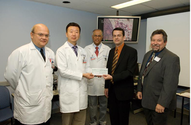 Di Wang, MD, second from left, accepts the Foundation telepathology grant check