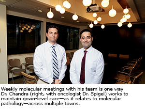 Weekly molecular meetings with his team is one way Dr. Chandra (right, with oncologist Dr. Spigel) works to maintain gown-level care—as it relates to molecular pathology—across multiple towns.