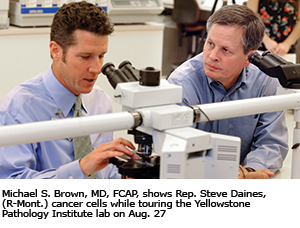Michael S. Brown, MD, FCAP, shows Rep. Steve Daines, (R-Mont.) cancer cells while touring the Yellowstone Pathology Institute lab on Aug. 27.