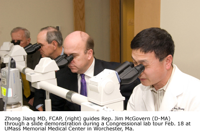 Zhong Jiang, MD, FCAP (right) guides Rep. Jim McGovern (D-MA) through a slide demonstration during a Congressional lab tour Feb. 18 at UMass Memorial Medical Center in Worchester, MA.