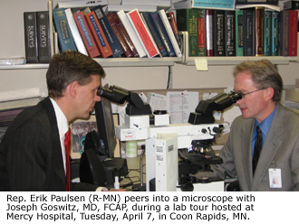 Rep. Erik Paulsen (R-MN) peers into a microscope with Joseph Goswitz, MD, FCAP, during a lab tour hosted at Mercy Hospital Tuesday, April 7 in Coon Rapids, MN.